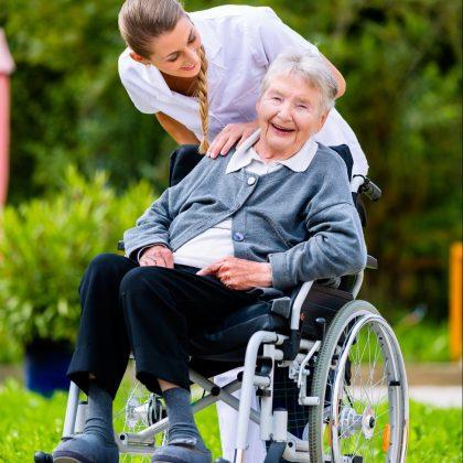 Frau in Rollstuhl mit Begleiterin